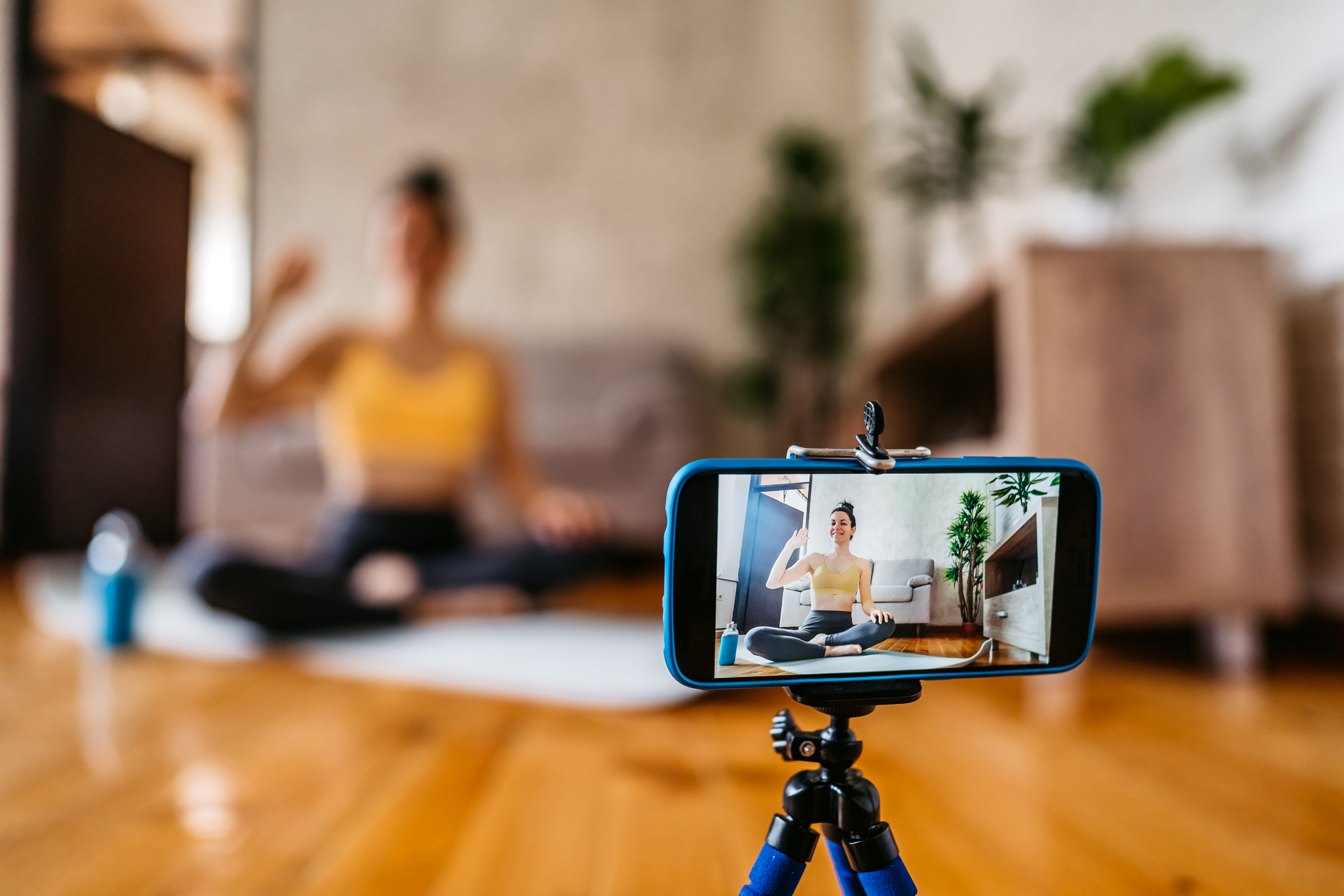 Beautiful young sporty woman vlogger practicing yoga from home.